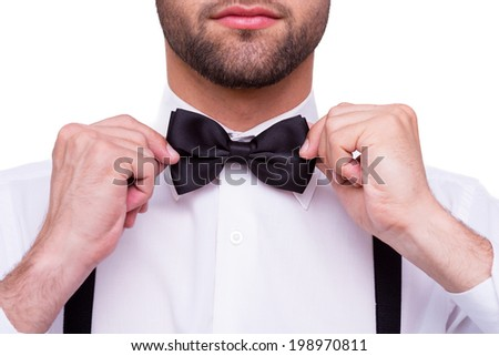 Man adjusting bow tie. Close-up of young man in white shirt adjusting his bow tie while standing isolated on white - stock photo