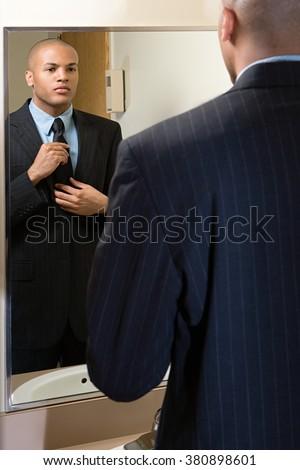 Man adjusting his tie in mirror - stock photo