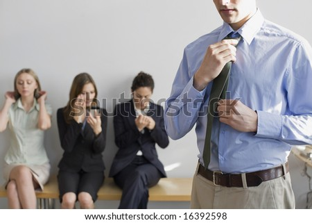 Man adjusting his tie, preparing for job interview, with fellow applicants in background - stock photo