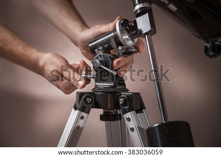 man adjusts a telescope closeup.