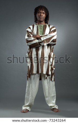 Man african in national cloth pose on gray background - stock photo