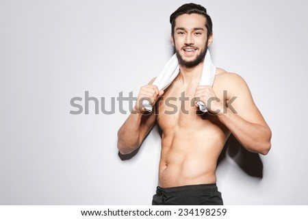 Man after workout. Handsome young man with towel on shoulders looking at camera and smiling while standing against grey background - stock photo