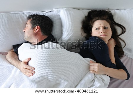 Man (age 35 -4 5) hogging the blanket from his woman in bed (Age 30-40) Couple lifestyle. Real people. copy space