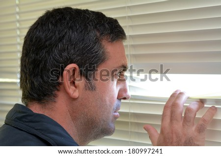 Man (age 35-40 ) looks out through Venetian blinds. Concept photo of curious, spy, nosy man. - stock photo