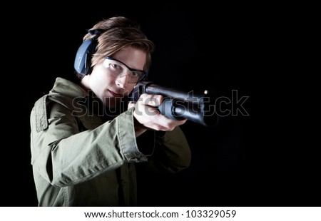 Man aiming a shot gun with protective gear - stock photo