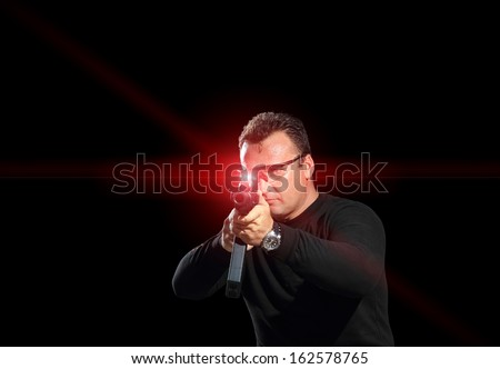 Man aiming assault rifle laser sight - stock photo