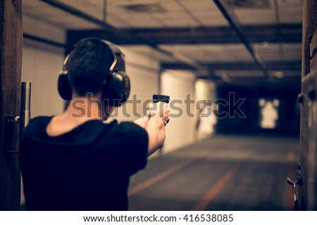Man aiming pistol at target in indoor firing range or shooting range - stock photo