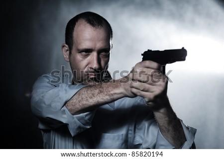 Man aiming pistol gun at night. Closeup. - stock photo