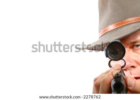 Man aiming riflescope at camera - stock photo