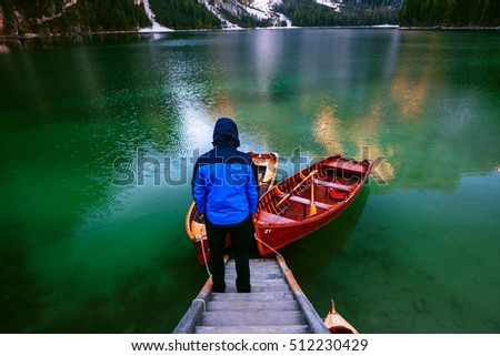 Man alone at the Braies Lake ( Pragser Wildsee ) in Dolomites mountains, Sudtirol, Italy