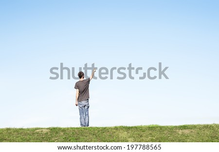 man alone in an empty landscape pointing to the sky
