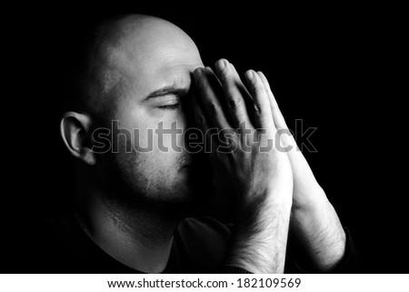 Man alone praying,low key and monochrome  - stock photo