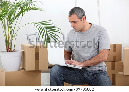 man amid removal boxes working on laptop - stock photo