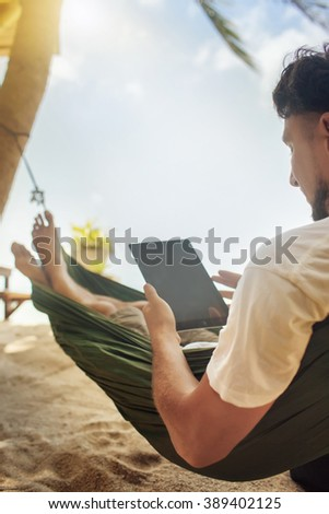 Man an using a digital tablet computer while relaxing in a hammock - stock photo