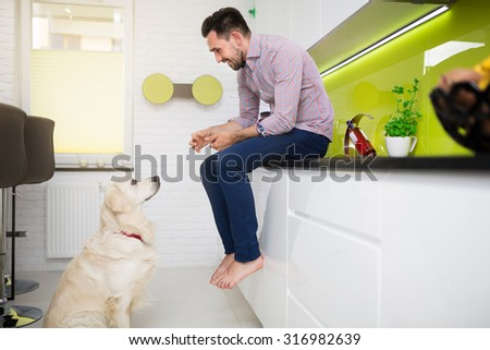 Man and a dog sitting in modern white kitchen - stock photo