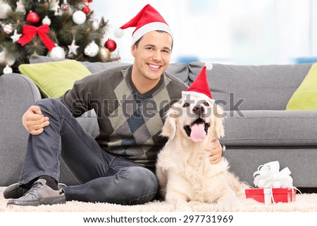 Man and a dog with Santa hats sitting by a sofa at home - stock photo