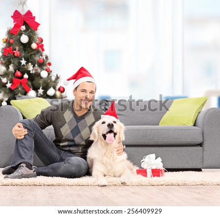 Man and a dog with Santa hats sitting by a sofa at home shot with tilt and shift lens - stock photo