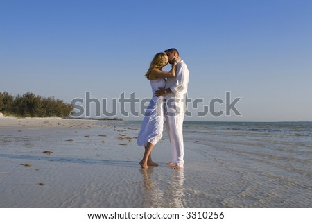 Man and a woman kissing on a beach.  Both wearing white clothes. - stock photo
