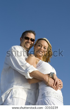 Man and a woman looking into the camera.  Both wearing white clothes. - stock photo