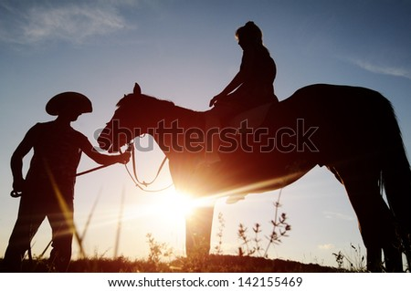 Man and a woman on horseback. - stock photo