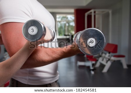 man and a woman (only arms and body) training with dumbbells  - stock photo