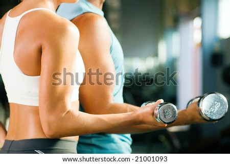 man and a woman (only arms and body) training with dumbbells (focus on weight, shallow depth of field) - stock photo