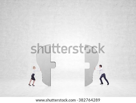 man and a woman pushing halves of a bulb to each other. Concrete background. Concept of cooperation.