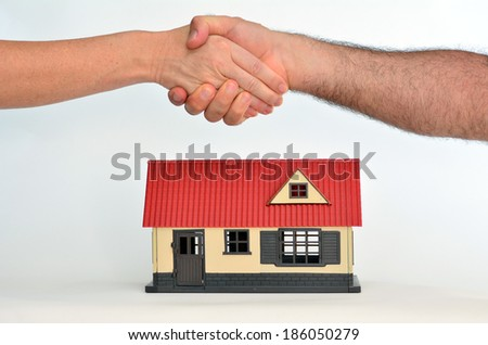 Man and a woman shaking hands over a toy house on white background - copy space.Concept photo of real estate business, home  Insurance, house rental, buying, renting, mortgage, selling, finance. - stock photo