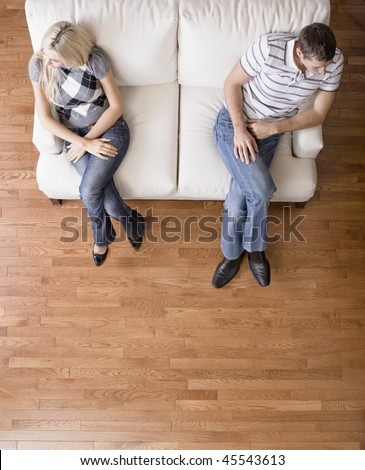 Man and a woman sit distantly on the ends of a cream colored love seat. Their heads are turned away from each other. Vertical shot. - stock photo