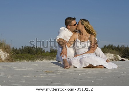 Man and a woman sitting on a beach, kissing.  Both wearing white clothes. - stock photo