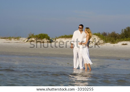 Man and a woman standing on a beach.  Both wearing white clothes. - stock photo