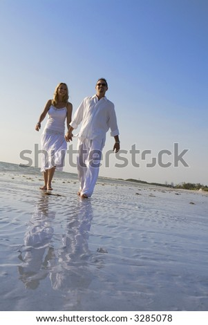 Man and a woman walking on a beach.  Both wearing white clothes.