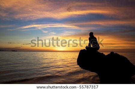 Man and beautiful sunset at tropical beach. - stock photo