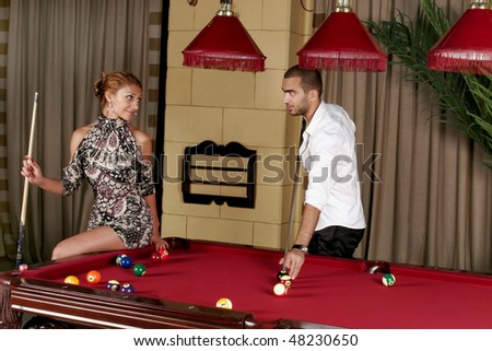 Man and beautiful woman, playing biliards on red table