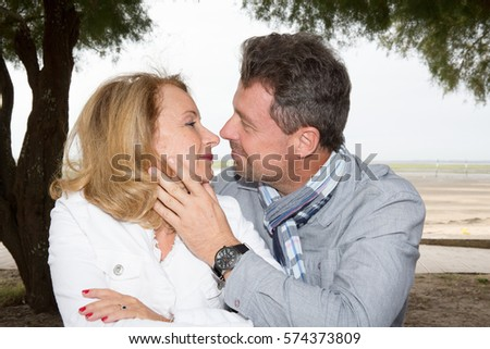 Man and blond woman kissing outdoor on holidays