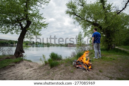 Man and bonfire in the spring forest. Coals of fire - stock photo