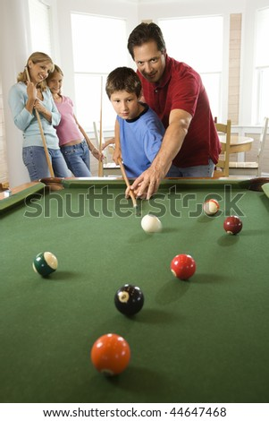 Man and boy playing pool with woman and girl in background. Vertically framed shot. - stock photo