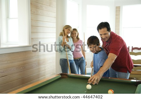 Man and boy shooting pool with woman and girl in background. Horizontally framed shot. - stock photo