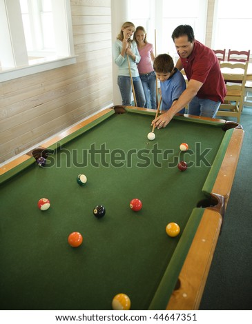 Man and boy shooting pool with woman and girl in background. Vertically framed shot. - stock photo