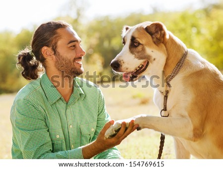 Man and central Asian shepherd in park. He is holding a dog's paw and smiles. - stock photo