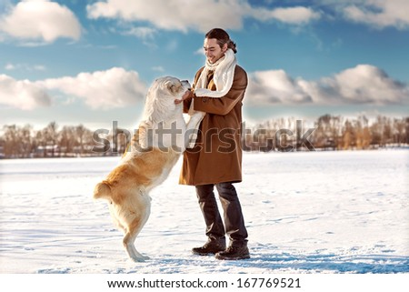 Man and central Asian shepherd playing with his dog outdoors - stock photo