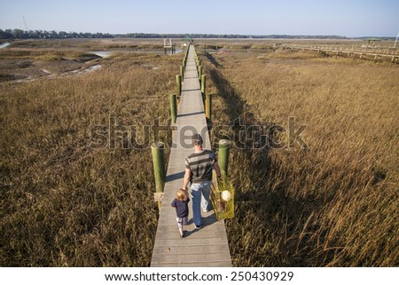 man and child going fishing on dock with crab trap, overhead view - stock photo