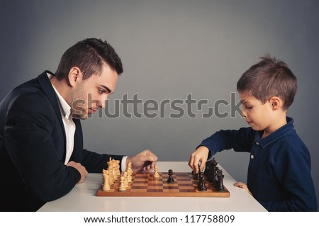 Man and child playing chess, isolated on dark background. - stock photo