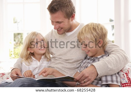 Man and children reading together - stock photo