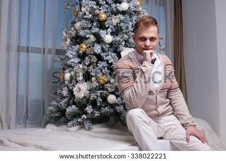 man and Christmas tree at home - stock photo