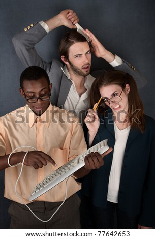 Man and cross-eyed woman work while handsome man combs his hair - stock photo