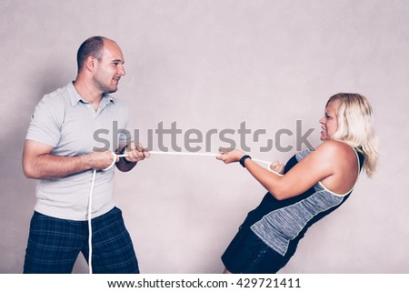 Man and determined sporty woman pulling a rope. Competition, determination and effort concept. - stock photo