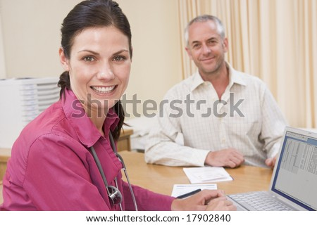 Man and doctor sat in office smiling - stock photo