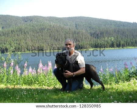Man and dog by the lake - stock photo