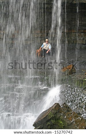 Man and Dog looking through sheet of Water from behind Ashgill  Force located near to the small and attractive isolated market town of Alston in Cumbria's Eden district - stock photo